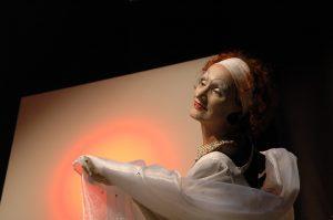 Eine Schauspielerein zeigt auf eine leere Leinwand. Sie trägt ein verträumtes, weißes Kleid.
