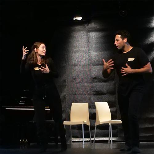 Zwei Spielende stehen auf der schwarzen Bühnen und zeigen mit strken GEsten eine Auseinandersetzung