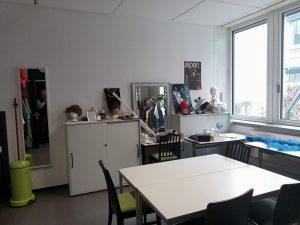 Der Schminkplatz. Zu sehen ist ein schöner alter Spiegel mit silbernen Holzrahmen. Links und rechts davon sind graue Aktenschränke. Alle Flächen sind voll mit Schminksachen. Reichlich unübersichtlich.